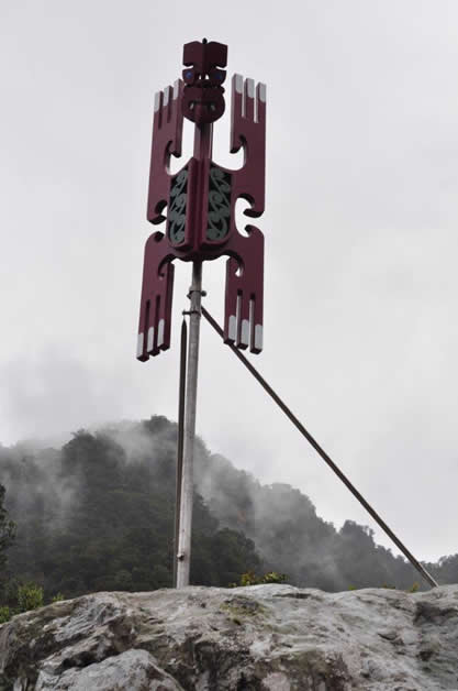 'Kahukura' The first poupou unveiled rises majestically with a background of forest and mist in the Fiordland National Park.