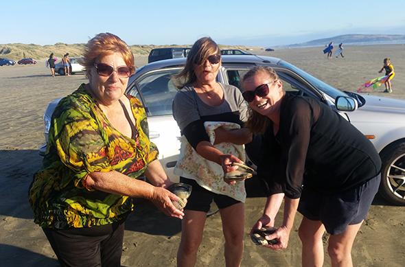 Ailene Stehlin, Jackie Genge and Ann Forbes getting toheroa at Ōreti Beach.
