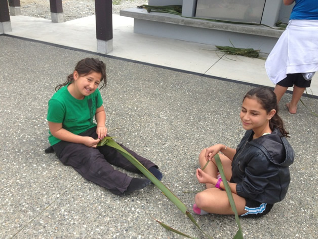 Aleigha Ngaamo and Leisi Pousini weaving putiputi harakeke.