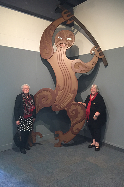 Aunty Jane Davis and Shona Fordyce standing beneath the carving of Tū Te Rākiwhanoa.