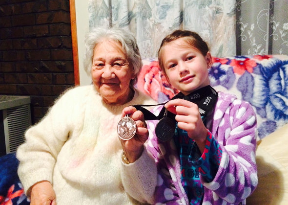 Esther showing off her medals. She is seated with her great-grandmother, Harriet Papuni.
