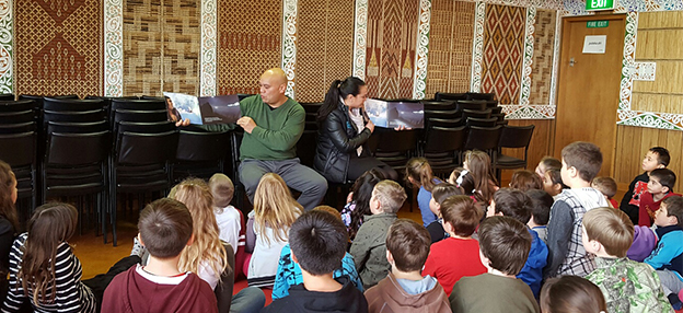 From left, Paddy Daintith and Tory Weatherall reading Māori and English versions of a story to the students of Bluff Community School.