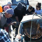 Gathering around the boat to look at the flounder.