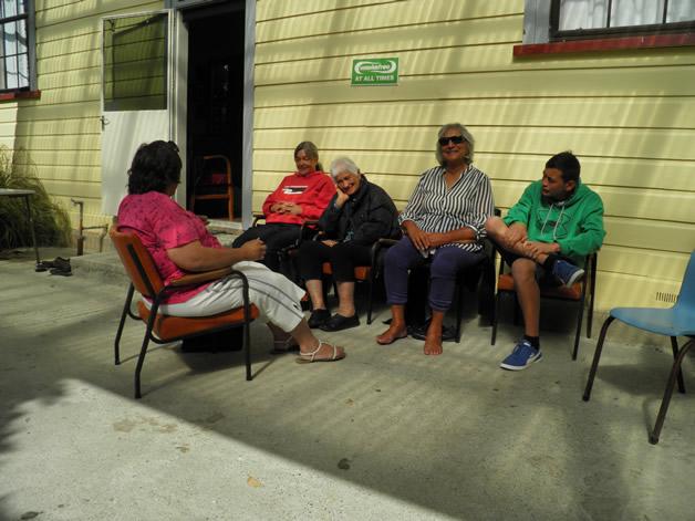 Kaumātua relaxing outside the whare.