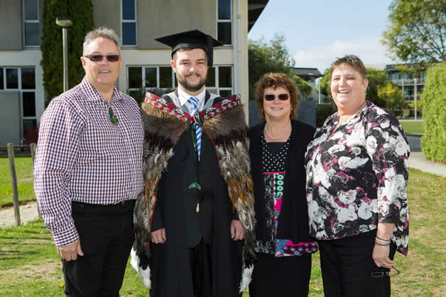 Liam with his whānau. Liam is wearing the korowai that his Aunty Christine made for him.