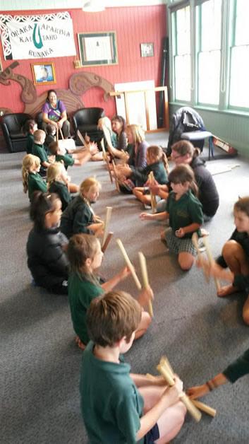 Marama Cooper teaches the children a Māori stick game.