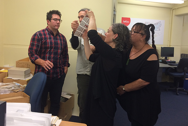 Ngāi Tahu Archive Team visit with Bill Dacker. Left to right: Takerei Norton, Bill Dacker, Helen Brown and Robyn Walsh look at a sleeve of negatives from the Bill Dacker photograph collection.