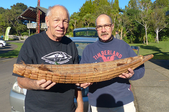 Papa Bones Rissetto (left) and Andrew Guy holding the model mōkihi, the model is close to 100 years old.