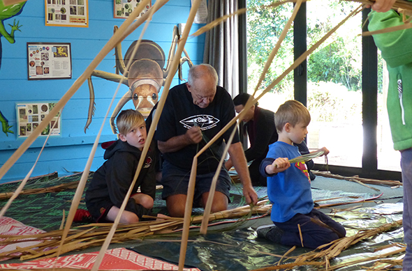 Papa Bones and tamariki constructing mōkihi.