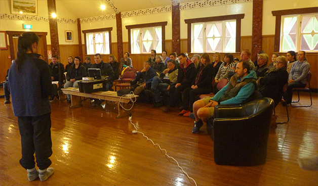 Parents, staff and peers listen and watch one of the presentations.
