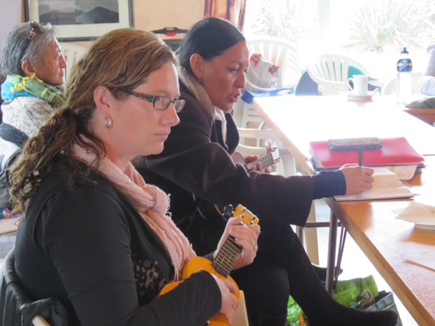 Participants strum their ukulele and learn during Judy McDowall's facilitation.