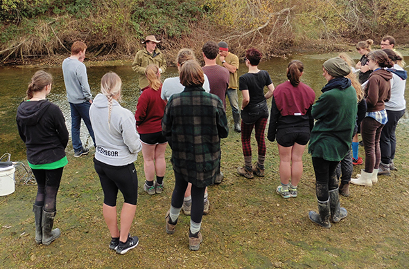 Pete Russell and Brendan Flack briefing volunteers on the bank of the Waikouaiti River.