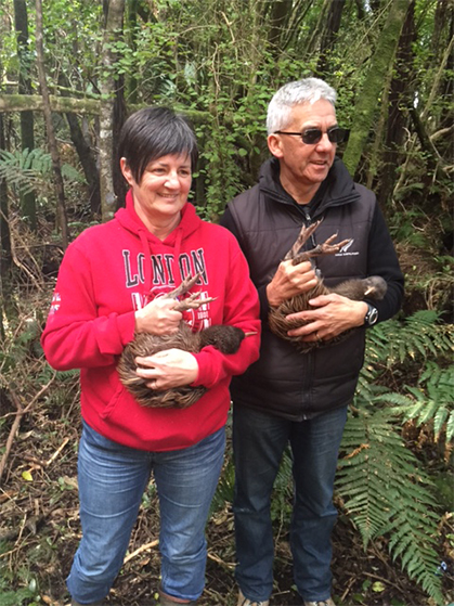 Riki and Lynley holding a pair of kiwi.