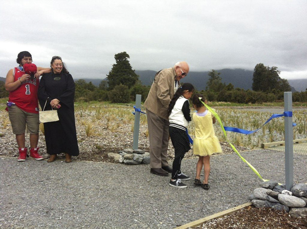 Tā Tipene and his little helpers Karera Wallace-Jones and Hariata Russell, cut the ribbon at Lake Matheson, watched by Tutoko and Susan Wallace.