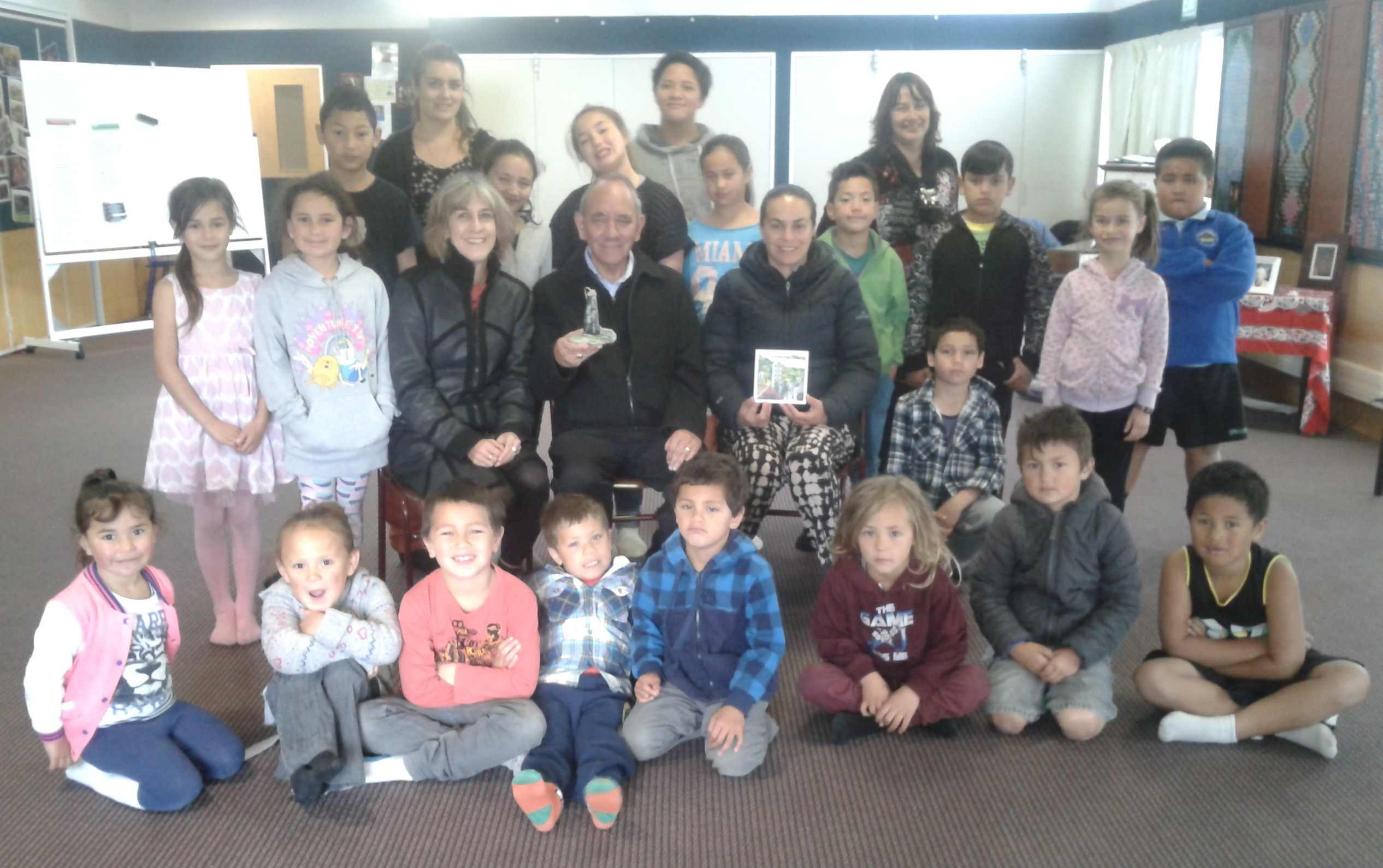 Tama Smith and Katharina Ruckstuhl with teachers and pupils at presentation of the taonga pounamu.