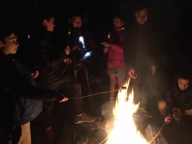 Tamariki gathering around the bonfire.