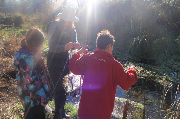 Tamariki with Sophie from Waterwise setting out eel nets on the Awarua River.