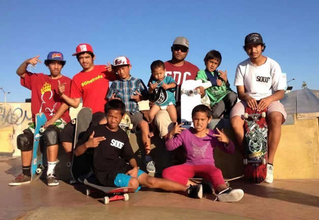 The Stone-Kelly skateboarding whānau. Dad (Meka) is holding Kahlei in the centre, surrounded by Kahlei's skateboarding siblings.