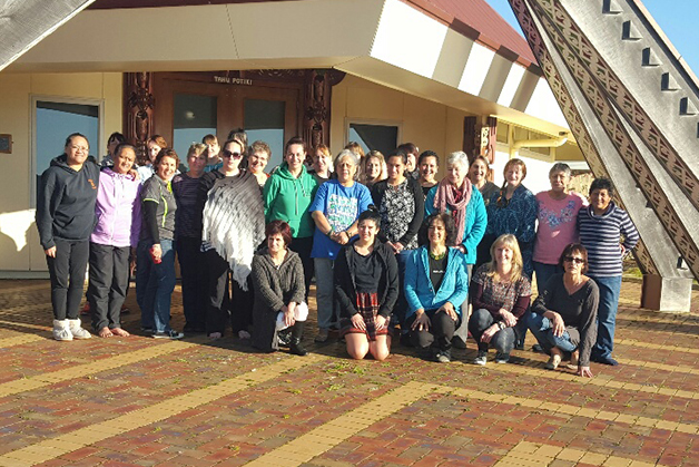The group of weavers standing outside the marae.