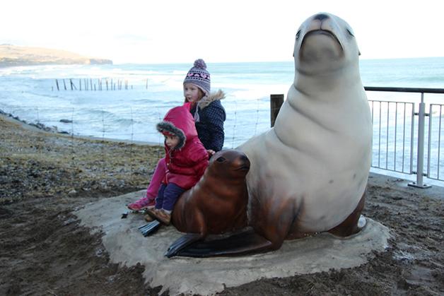 The tamariki enjoyed sitting on the statue. Photo by Neville Peat.