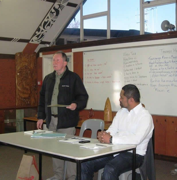 Uncle Terry Ryan speaking to whānau at the Tauranga bi-monthly hui with Chair Huey Rurehe seated.