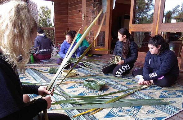 Wāhine weaving harakeke.