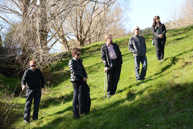 Whānau and councillors stand on the hillside at Takapuneke.